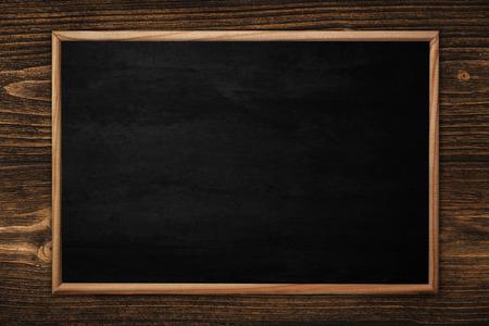 Pizarra abstracta o pizarrón con marco sobre fondo de madera. espacio vacío para agregar texto. Foto de archivo