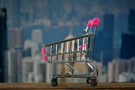 Shopping cart or supermarket trolley on top wooden working table with city and office building background, business and financial concept idea. Imagens