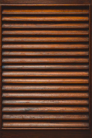 Wooden slatted fence or lath front showcase cabinet or wardrobe, frame door and drawers made from dark wood, background and texture, interior design. texture. Stock Photo