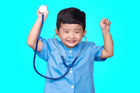 Smiling Asian kid in blue medical uniform holding stethoscope looking at camera on blue green background with copy space, healthy concept idea. Standard-Bild - 123143217