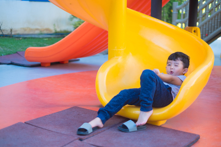 Asian kid playing slide at the playground under the sunlight in summer, Happy kid in kindergarten or preschool school yard.