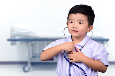 Asian Thai kid with medical stethoscope looking at camera, healthy concept idea. 免版税图像