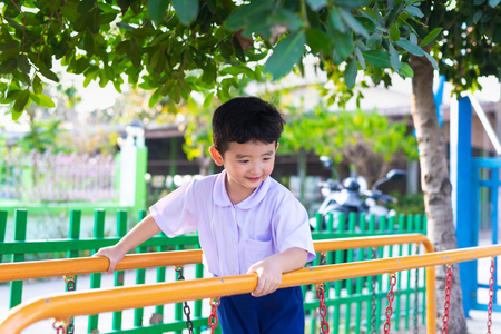 Asian boy hang the monkey bar or balance bar for balance at outdoor playground in summer. Фото со стока