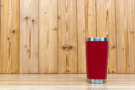 Red colour stainless steel tumbler or cold and hot storage cup on wooden background. 版權商用圖片 - 124557932