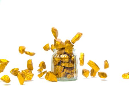 Falling gold nuggets, gold ore , precious stone or lump of golden stone and glass jar isolated on white background.