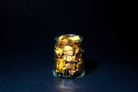 Gold nuggets, gold ore , precious stone or lump of golden stone and glass jar in dark room.