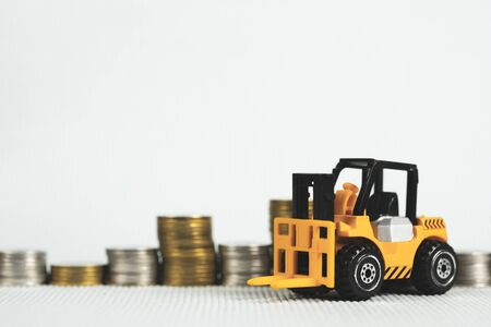 toy forklift truck with coin stack, business finance and banking industrial concept idea.