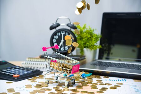 Falling gold coins in shopping cart or supermarket trolley on working table with office supplies or office work essential tools items for business financial concept