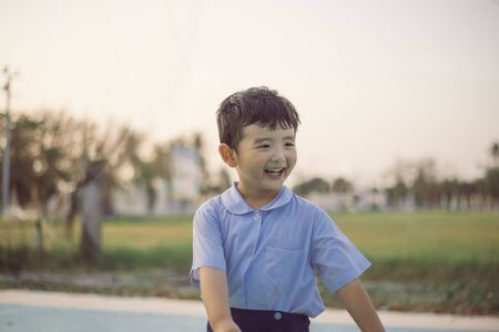 Outdoor portrait of a happy Asian student kid in school uniform smiling with copy space for add text or word.