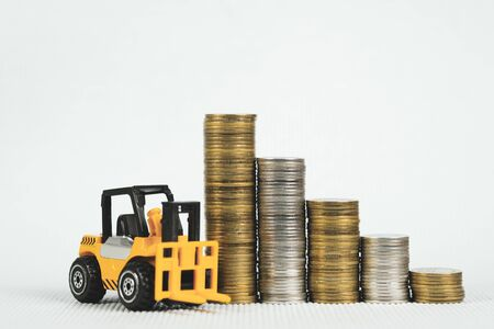 Mini forklift truck with coin stack, business finance and banking industrial concept idea.