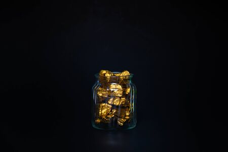 Gold nuggets, gold ore, precious stone or lump of golden stone and glass jar in dark room. Фото со стока