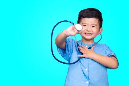 Enfant asiatique souriant en uniforme médical bleu tenant un stéthoscope regardant la caméra sur fond vert bleu avec espace de copie, idée de concept sain. Banque d'images