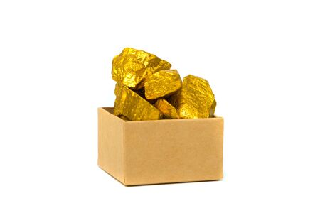 Gold nuggets, gold ore, precious stone or lump of golden stone and cardboard box isolated on white background. Фото со стока
