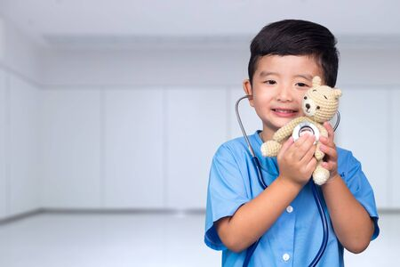 Smiling Asian kid in blue medical uniform holding stethoscope looking at camera, healthy concept idea. Фото со стока