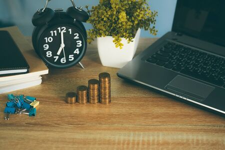 Coin stack and financial graph paper sheet with notebook calculator and alarm clock on working table, business finance concept idea.