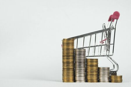 stacks of coins and shopping cart or supermarket trolley, business finance shopping concept.