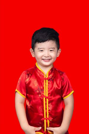 Chinese New Year Concept, Cute Asian boy in red traditional Chinese suit isolated on red background