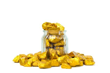 Gold nuggets, gold ore, precious stone or lump of golden stone and glass jar isolated on white background.