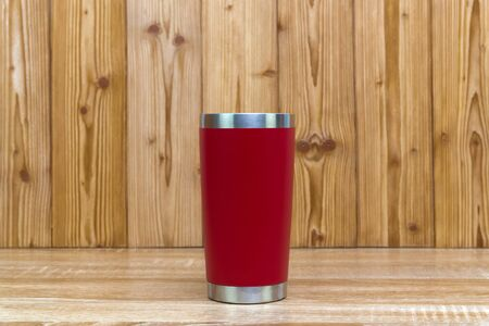 Red colour stainless steel tumbler or cold and hot storage cup on wooden background.