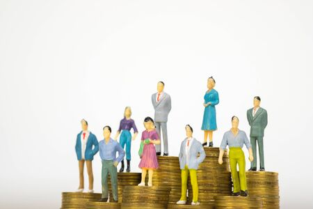 Figure miniature businessman or small people investor and office worker secretary standing on coin stack, for money and financial business success concept idea.