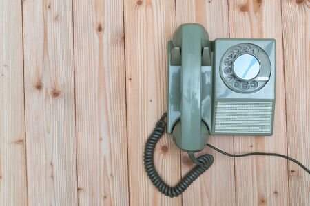 Retro rotary telephone or vintage phone with cable on wood table, wooden background, top view with copy space, vintage communication concept.