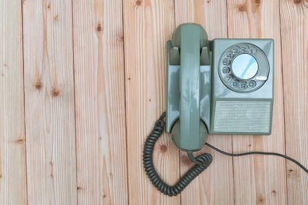 Teléfono rotatorio retro o teléfono vintage con cable sobre mesa de madera, fondo de madera, vista superior con espacio de copia, concepto de comunicación vintage.