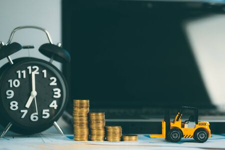 Miniature mini forklift truck with coin stack on working table with office supplies or office work essential tools items for business financial concept