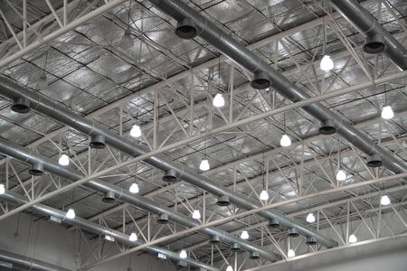 Air condition system tube with lighting lamp electrical system and aare skin ceiling of insulated metal roof inside building. Stok Fotoğraf