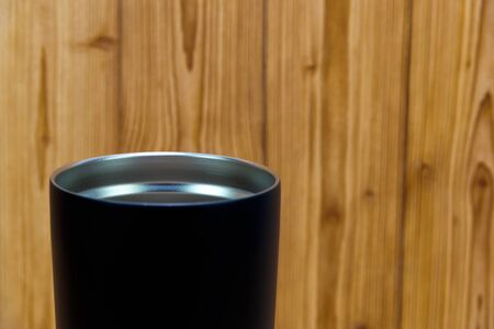 Black colour stainless steel tumbler or cold and hot storage cup on wooden background.