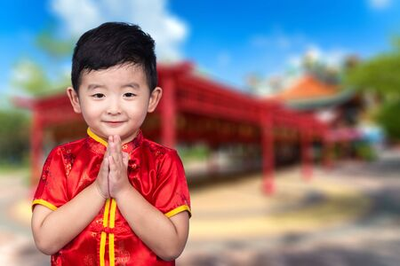 Happy Asian Chinese kid wearing red traditional suit on Chinese temple or joss house background celebration for Chinese New Year concept.