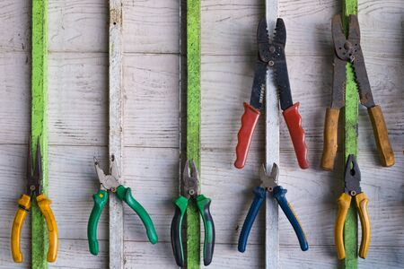 Old hand tools hanging on wall in workshop or auto service garage, many tool shelf against a wall, repair and car mechanic concept.