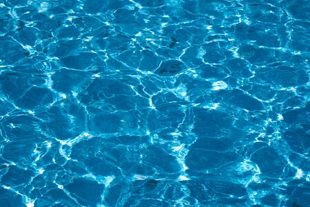 Blue and bright ripple clean water surface in swimming pool with sun reflection. Stockfoto