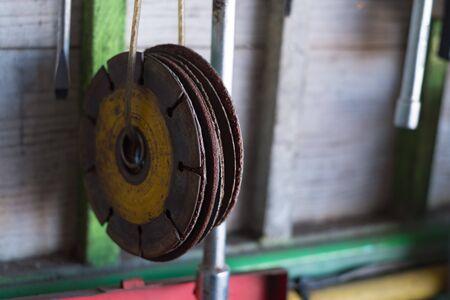 Circular wire grinding brush machine. Steel polisher in garage.