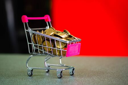 Coins in supermarket cart trolley on the table, business concept