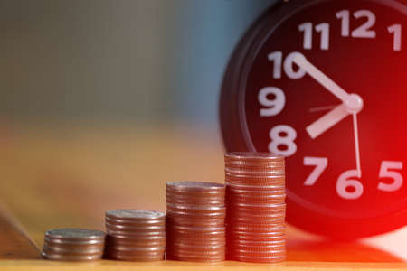 Alarm clock and step of coins stacks on working table, time for savings money concept, banking and business idea. soft tone.