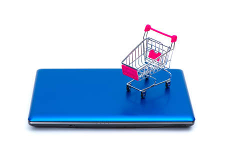 Shopping cart or supermarket trolley with laptop notebook isolated on white background and copy space, e-commerce and online shopping concept. Imagens