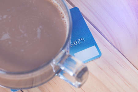 Credit card and glass of hot coffee on wooden table in the morning, soft tone. shallow focus