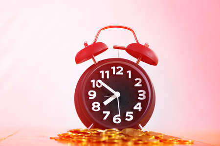 Alarm clock and piles of coin on working table, time for savings money concept, banking and business idea. soft tone. Imagens