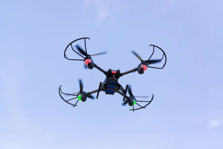 Flying drone of quad copter in clear blue sky