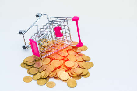 Stack of coins and shopping cart or supermarket trolley on white background, business finance shopping concept.