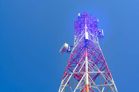 Mobile phone communication antenna tower with satellite dish on blue sky background, Telecommunication tower, soft tone