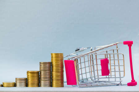 Step of stacks of coins and shopping cart or supermarket trolley on grey background, business finance shopping concept.