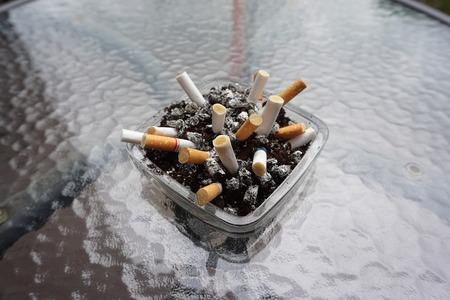 cigarette stub in coffee residue Reklamní fotografie