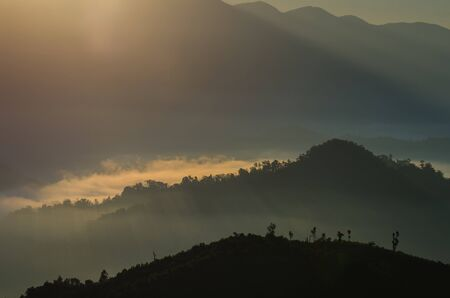 A view from mountains to the valley with light and fog