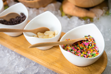 jimmies: Sprinkle colorful jimmies for cake decoration or ice cream topping. In white cup placed on wood Stock Photo