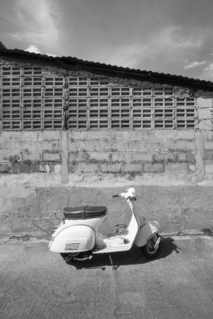 white Classic Vespa scooter stands parked near the concrete old wall,white Vespa scooter stands parked near the concrete old wall with blue sky background,white Classic Motorcycles(monochrome),black and white background