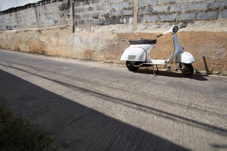 vespa piaggio: white Classic Vespa scooter stands parked near the concrete old wall,white Vespa scooter stands parked near the concrete old wall background,white Classic Motorcycles