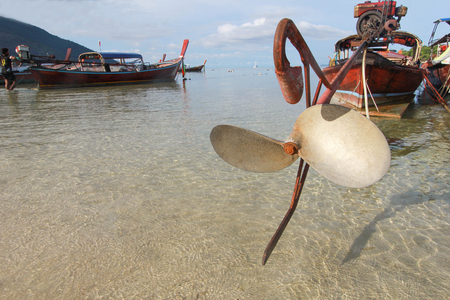 con dao: close up Longtail boat propeller and beautiful ocean with blue sky of Koh Lipe island, Thailand