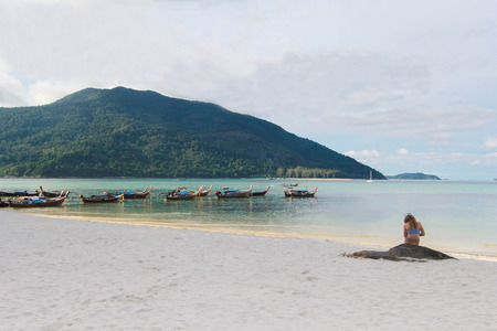 con dao: mermaid on the beach with Longtail boat and beautiful ocean with blue sky of Koh Lipe island, Thailand