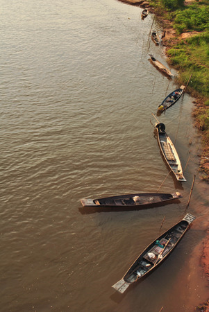 Traditional Thai rowing boats are located in the Chi River Stock Photo